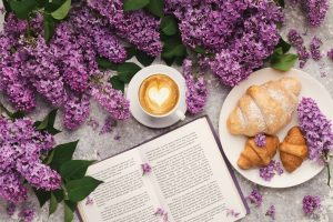 Spring background with lilac, coffee and book